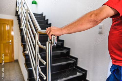 Fotografia, Obraz  chrome fence on staircase. hand holds stainless steel fence