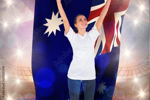 Aluminium Prints Excited football fan in white cheering holding australia flag against large football stadium under bright blue sky