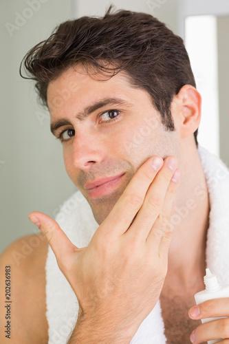 Fotografie, Obraz  Man applying moisturizer on face