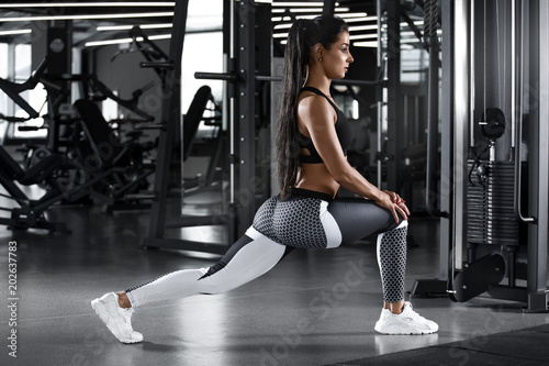 Fotografía  Fitness woman doing lunges exercises for leg muscle workout training in gym