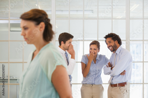 Fototapeta Colleagues gossiping with sad businesswoman in foreground obraz