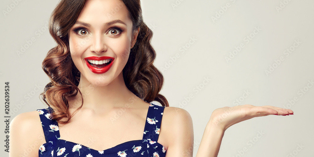 Fototapeta Woman surprise showing product .Beautiful girl  with curly hair and red lips pointing to the side . Presenting your product. Expressive facial expressions
