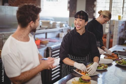 Cheerful waiter and female chef working in kitchen