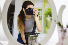 Pretty Cool Young Caucasian Woman. The Girl Takes Pictures In The Mirror On A Professional Camera. Selfie In The Mirror.