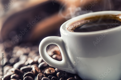 Photo sur Toile Cafe Cup of black coffee with beans on wooden table
