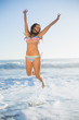Laughing woman in bikini jumping in the sea