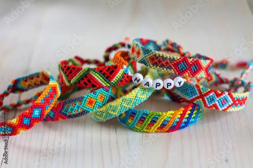 02f231b42634f handmade friendship bracelets with colorful threads on light ...