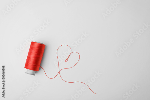 Fotografía Heart made of color sewing thread and spool on white background, top view
