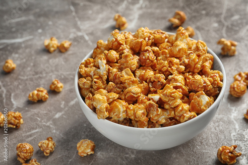 Delicious popcorn with caramel in bowl on table