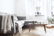 Leinwanddruck Bild - Stylish interior of living room with small design table and sofa. White walls, plants on the windowsill. Brown wooden parquet.