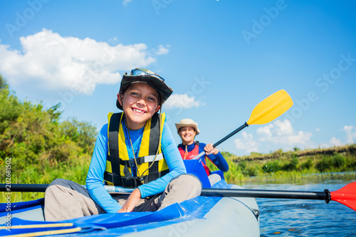 Fototapeta Happy boy kayaking on the river on a sunny day during summer vacation