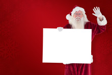 Santa Holds A Sign And Is Waving Against Red Background