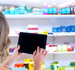 Rear view of woman using tablet pc against close up of shelves of drugs
