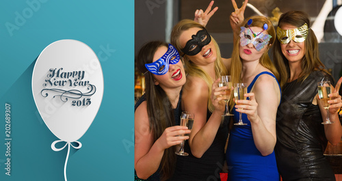 attractive women wearing masks holding champagne against classy new year greeting