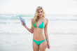 Content blonde woman in green bikini holding a tablet pc