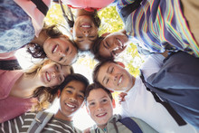 Portrait Of Smiling School Kids Forming A Huddle In Campus
