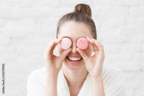 Fotobehang Macarons Indoor closeup of young good-looking European Caucasian female pictured in white bathrobe against white brick background holding colorful macarons in front of eyes having much fun feeling excited