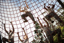 Military Soldiers Climbing Rope During Obstacle Course