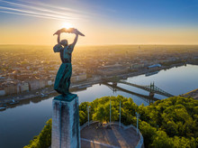 Budapest, Hungary - Aerial View Of The Beautiful Hungarian Statue Of Liberty With Liberty Bridge And Skyline Of Budapest At Sunrise With Clear Blue Sky