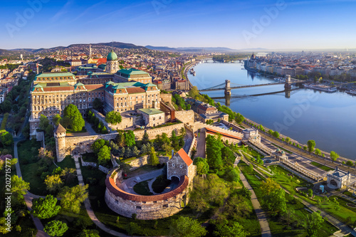 Budapest, Hungary - Aerial panoramic skyline view of Buda Castle Royal Palace with Szechenyi Chain Bridge, Hungarian Parliament and Matthias Church at sunrise with clear blue sky