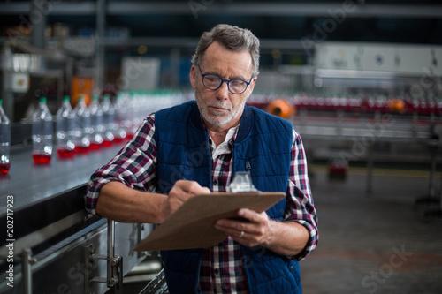 Fototapeta Male factory worker maintaining record on clipboard obraz na płótnie