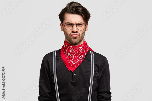 Photo Portrait of grumpy handsome male frowns face in dissatisfaction, has discontent upset look, wears fashionable shirt, red bandana isolated over white background