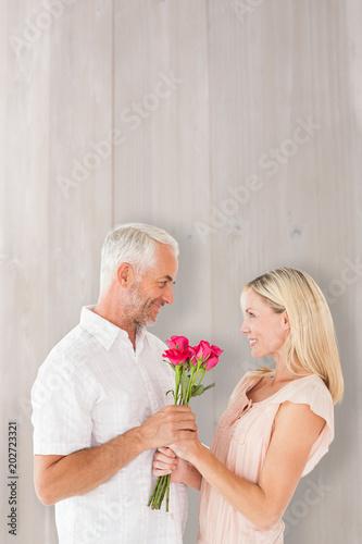 Fototapeta  Affectionate man offering his partner roses against bleached wooden planks backg