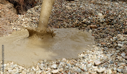Fotografie, Obraz  Liquid soil is poured from the concrete mixer onto the floor of the excavation pit covered with coarse gravel and stones
