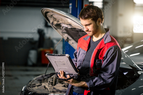 Mechanic using laptop on car at repair garage