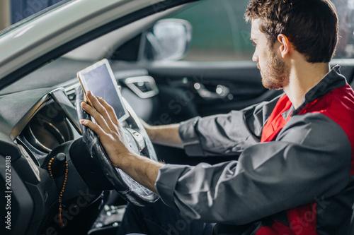 mechanic sitting in car doing diagnostics on digital tablet