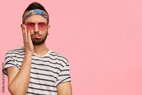 Fotografie, Obraz  Photo of displeased puzzled male hippie with stubble, keeps hand on cheek and lo