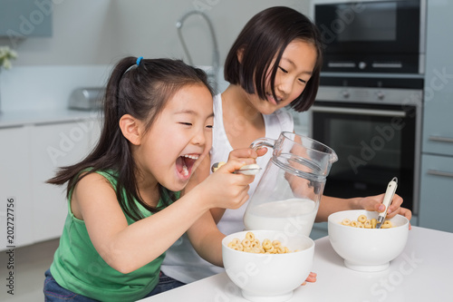 Fotografia, Obraz  Two happy young girls eating cereals in kitchen