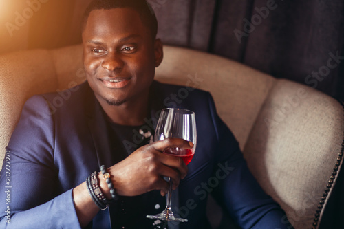 Tuinposter Bar Happy young dark-skinned student dressed in cute jacket with rosary and bracelets put on his hand, sitting in big chair