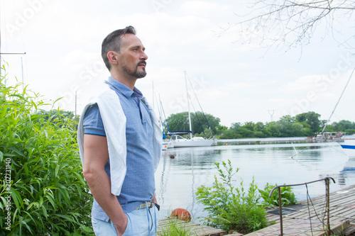 Fotografía  Handsome yachtsman standing on river pier