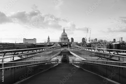 Millennium bridge with Saint Paul Cathedral in the evening in London, UK. Bridge over river Thames. Black and white