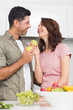 Couple with fruits looking at each other in kitchen
