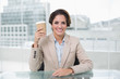 Smiling businesswoman holding disposable cup at her desk