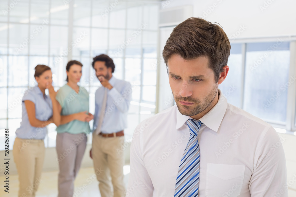 Fototapety, obrazy: Colleagues gossiping with sad businessman in foreground