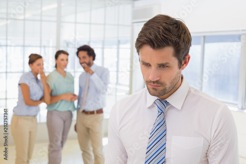 Fototapeta Colleagues gossiping with sad businessman in foreground obraz