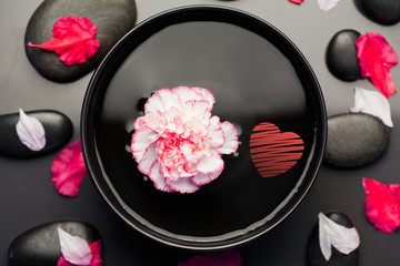 Obraz na płótnie Canvas red heart against white and pink carnation floating in a black bowl surrounded by black stones and petals