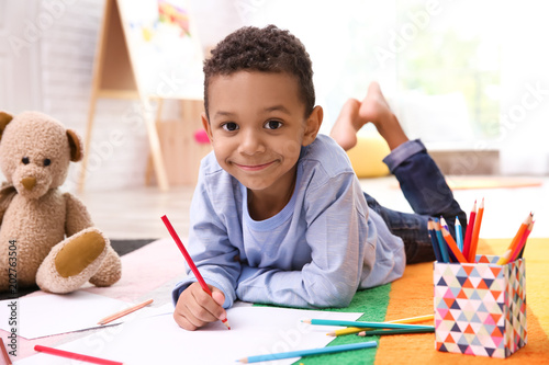 Little African-American boy drawing on floor indoors