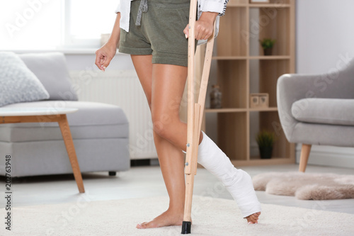 Fényképezés Young woman with crutch and broken leg in cast at home