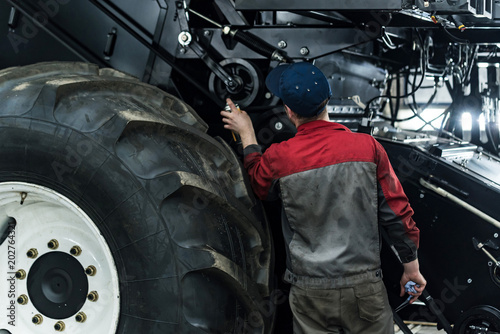 Industrial worker assembles agricultural equipment