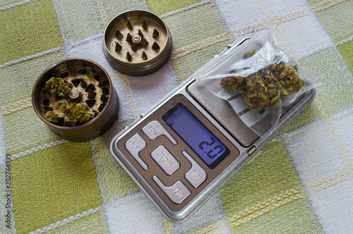 Small digital weighing machine of precision with a plastic bag with two grams of marijuana and grinder with buds Tableau sur Toile