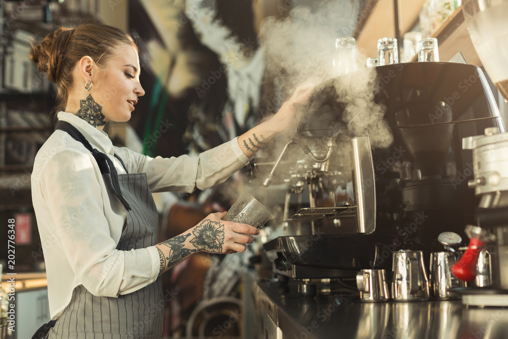 Fototapeta Tattooed barista making coffee in professional coffee machine