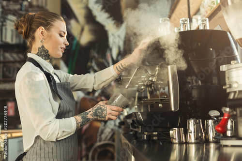 Tattooed barista making coffee in professional coffee machine Wallpaper Mural