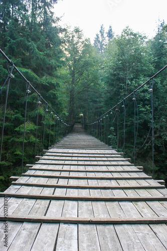 Suspended wooden bridge across the mountain river.