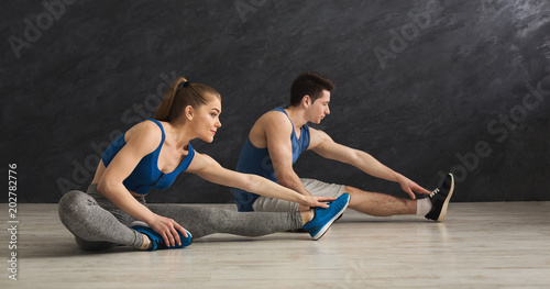 Leinwand Poster Fitness couple at stretching training indoors