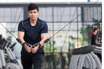 Athletic young man exercising equipment at gym, workout in fitness center.