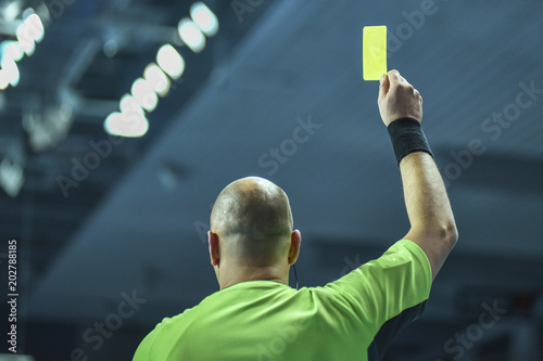 Referee shows yellow card during handball match.